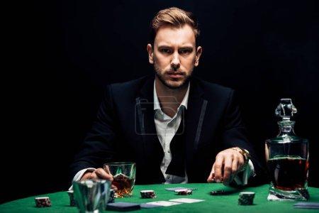 Photo pour Foyer sélectif de l'homme tenant poking chips et verre avec de l'alcool isolé sur noir - image libre de droit