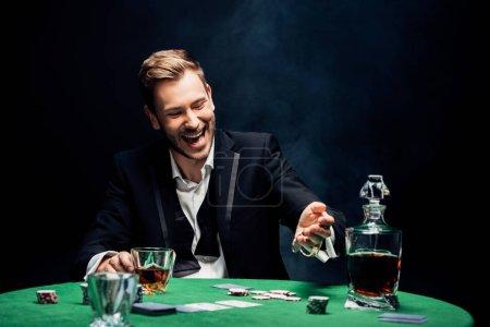 Foto de Enfoque selectivo del hombre feliz que tiene vidrio con alcohol en negro con humo - Imagen libre de derechos