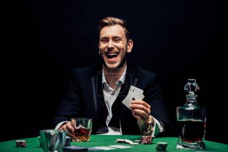 Photo pour KYIV, UKRAINE - 20 AOÛT 2019 : mise au point sélective d'un homme joyeux tenant un verre avec de l'alcool et jouant aux cartes isolées sur du noir - image libre de droit