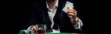 Photo pour KYIV, UKRAINE - 20 AOÛT 2019 : prise de vue panoramique d'un homme tenant des cartes à jouer isolées sur du noir - image libre de droit