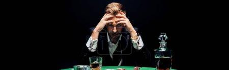 Photo pour Photo panoramique d'un homme triste assis près d'une table de poker isolé sur noir - image libre de droit