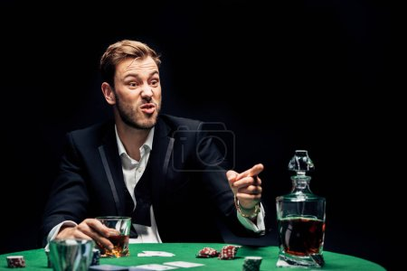 Photo for Selective focus of angry man pointing with finger near alcohol and playing cards isolated on black - Royalty Free Image