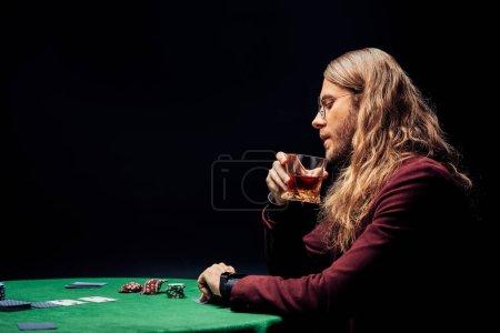 Photo pour Vue latérale de l'homme dans des lunettes tenant verre avec whisky isolé sur noir - image libre de droit