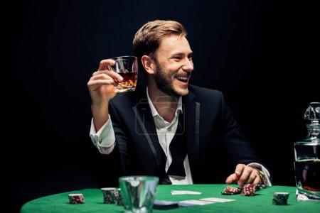 Photo pour Foyer sélectif de l'homme souriant tenant verre avec de l'alcool isolé sur noir - image libre de droit