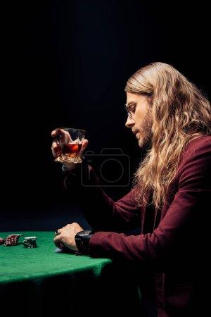 Photo pour Vue latérale de bel homme dans des lunettes de vue tenant verre avec whisky isolé sur noir - image libre de droit