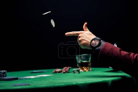 Photo pour Homme de vue recadrée jetant dans les jetons de poker d'air d'isolement sur le noir - image libre de droit