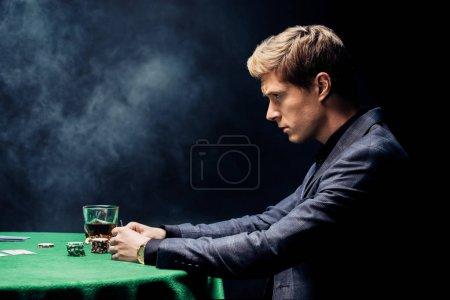 Photo pour Vue latérale d'un bel homme jouant au poker sur noir avec de la fumée - image libre de droit