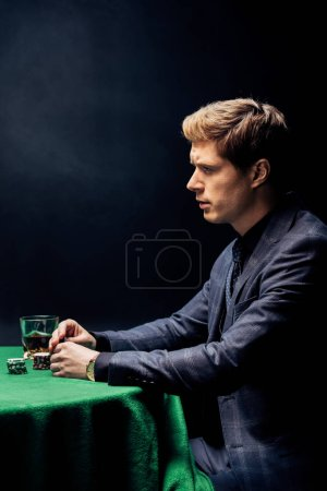 Photo for Side view of man playing poker on black with smoke - Royalty Free Image