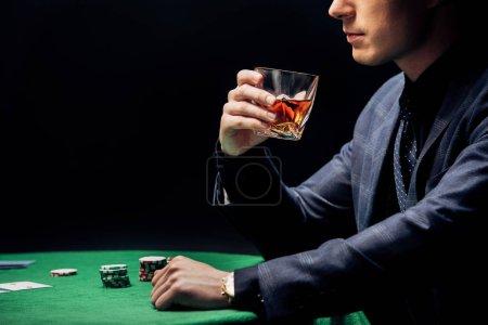 Photo pour Vue recadrée de l'homme tenant un verre de whisky et jouant au poker isolé sur noir - image libre de droit
