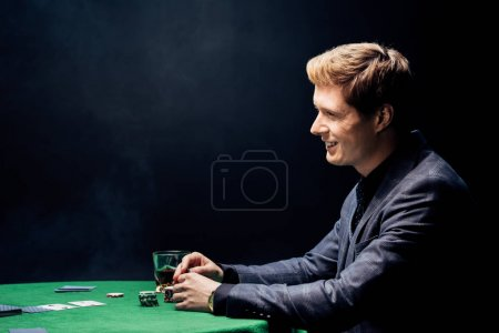 Photo pour Side view of happy man playing poker on black with smoke - image libre de droit