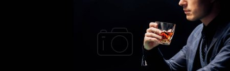Photo pour Tir panoramique de l'homme retenant le verre avec le whiskey d'isolement sur le noir - image libre de droit