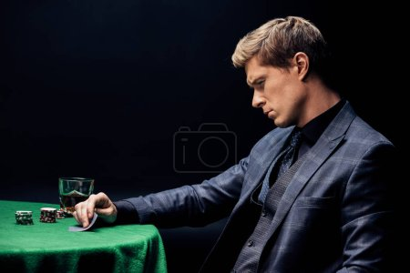 Photo pour Kyiv, Ukraine - August 20, 2019 : handsome man looking at playing cards while playing poker on black - image libre de droit