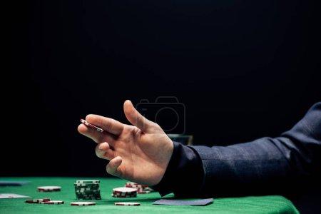 Photo pour KYIV, UKRAINE - 20 AOÛT 2019 : vue recadrée de l'homme tenant pièce de poker tout en faisant pari isolé sur noir - image libre de droit