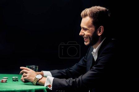 Photo pour Heureux homme barbu souriant près de la table de poker isolé sur noir - image libre de droit