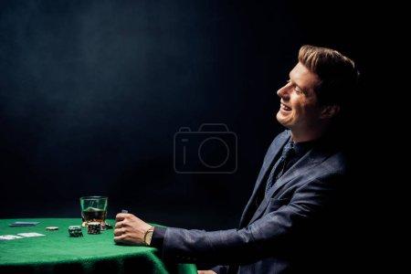 Foto de Hombre alegre sonriendo cerca de la mesa de póquer con vaso de whisky en negro - Imagen libre de derechos