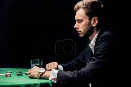Photo pour Vue latérale de l'homme contrarié jouant au poker près d'un verre de whisky isolé sur noir - image libre de droit