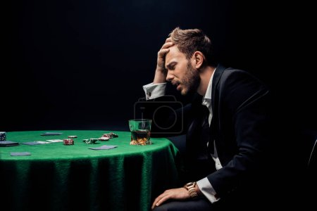 Photo pour Kyiv, Ukraine - 20 août 2019 : side view of sad man playing poker near glass of whiskey isolated on black - image libre de droit