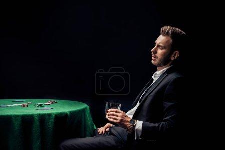 Photo pour Homme barbu bouleversé retenant le verre près de la table de poker d'isolement sur le noir - image libre de droit