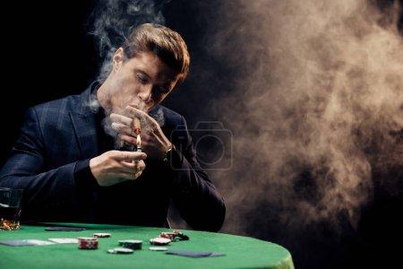 Photo pour Foyer sélectif de l'homme beau retenant plus léger tout en fumant sur le noir avec la fumée - image libre de droit
