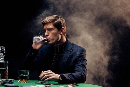 Photo pour Bel homme fumant le cigare sur le noir avec la fumée - image libre de droit