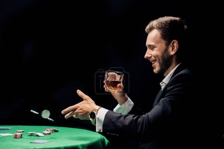 Photo for Happy man throwing in air poker chips isolated on black - Royalty Free Image