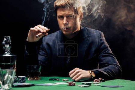 Photo pour Bel homme fumant cigare près de la table de poker sur noir avec de la fumée - image libre de droit