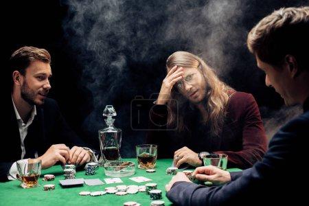 Photo pour Foyer sélectif des amis jouant au poker sur le noir avec de la fumée - image libre de droit