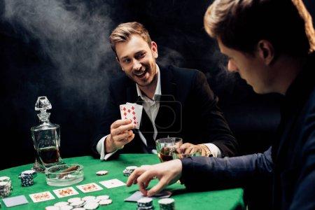 Photo pour KYIV, UKRAINE - 20 AOÛT 2019 : mise au point sélective d'un homme heureux tenant des cartes à jouer sur du noir avec de la fumée - image libre de droit