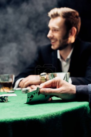 Photo pour KYIV, UKRAINE - AUGUST 20, 2019: selective focus of man touching playing cards near player on black with smoke - image libre de droit