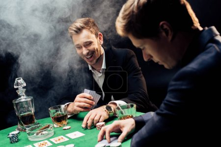 Photo pour Kyiv, Ukraine - 20 août 2019 : selective focus of cheerful man playing poker near friend and poker chips on black with smoke - image libre de droit