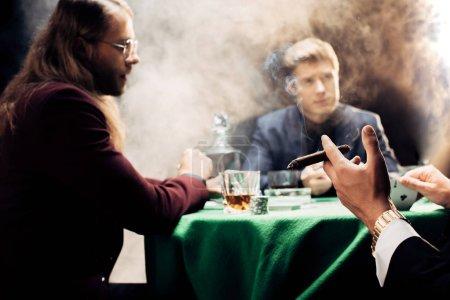 Photo pour Vue recadrée de l'homme tenant cigare tout en jouant au poker sur noir avec de la fumée - image libre de droit
