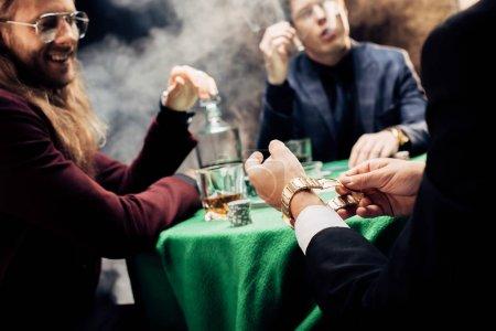 Photo pour Foyer sélectif de la montre de fixation de joueur tout en jouant au poker sur le noir - image libre de droit