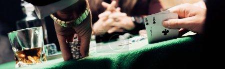 Photo pour KYIV, UKRAINE - 20 AOÛT 2019 : prise de vue panoramique de l'homme touchant les cartes à jouer et les jetons de poker près du joueur - image libre de droit