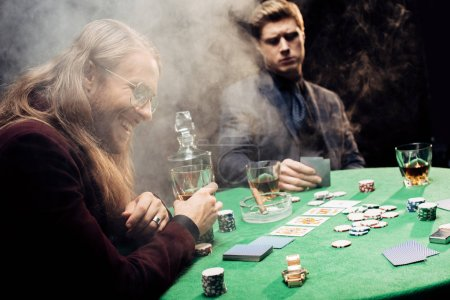 Photo pour Kyiv, Ukraine - August 20, 2019 : handsome men near poker table with poker chips and playing cards on black with smoke - image libre de droit