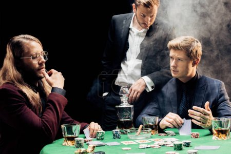 Photo pour Kyiv, Ukraine - 20 août 2019 : beautiful men gesturing while playing poker on black with smoke - image libre de droit