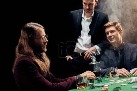 Photo pour Kyiv, Ukraine - 20 août 2019 : beautiful friends gesturing while playing poker on black with smoke - image libre de droit