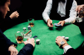 KYIV, UKRAINE - AUGUST 20, 2019: cropped view of men near croupier with playing cards isolated on black