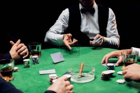 Photo for KYIV, UKRAINE - AUGUST 20, 2019: cropped view of men near croupier in formal wear with playing cards isolated on black - Royalty Free Image