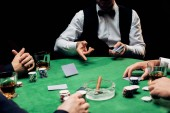 KYIV, UKRAINE - AUGUST 20, 2019: cropped view of men near croupier in formal wear with playing cards isolated on black