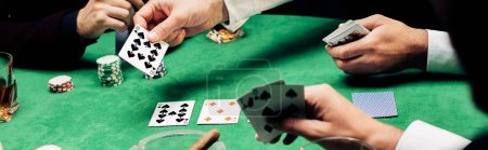 Photo pour Kyiv, Ukraine - August 20, 2019 : panoramic shot of men playing poker near poker table - image libre de droit
