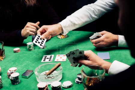 Photo pour Kyiv, Ukraine - August 20, 2019 : cropped view of men playing poker near poker table isolated on black - image libre de droit