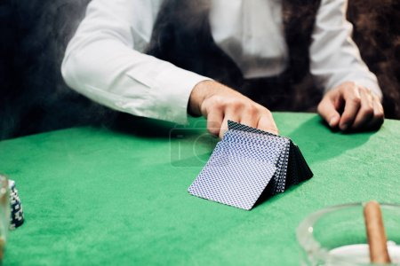 Photo pour Kyiv, Ukraine - August 20, 2019 : cropped view of croupier touching playing cards on black - image libre de droit