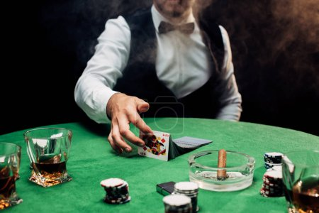 Photo pour Kyiv, Ukraine - August 20, 2019 : cropped view of croupier touching playing cards near poker table on black with smoke - image libre de droit