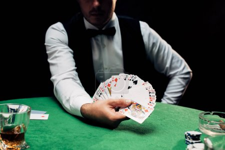 Photo pour Kyiv, Ukraine - August 20, 2019 : cropped view of croupier in formal wear holding playing cards near poker table isolated on black - image libre de droit