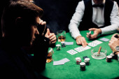 KYIV, UKRAINE - AUGUST 20, 2019: selective focus of man near poker table isolated on black