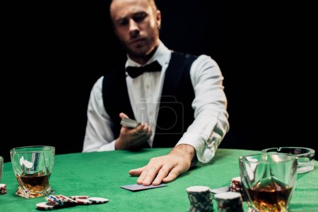 Photo pour KYIV, UKRAINE - AUGUST 20, 2019: selective focus of bearded croupier holding playing cards isolated on black - image libre de droit