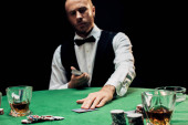 KYIV, UKRAINE - AUGUST 20, 2019: selective focus of bearded croupier holding playing cards isolated on black