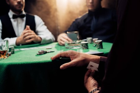 Photo pour KYIV, UKRAINE - AUGUST 20, 2019: cropped view of man cheating while playing poker on black with smoke - image libre de droit