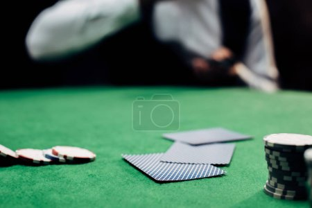 Photo pour Kyiv, Ukraine - August 20, 2019 : cropped view of man near playing cards and poker chips on poker table isolated on black - image libre de droit