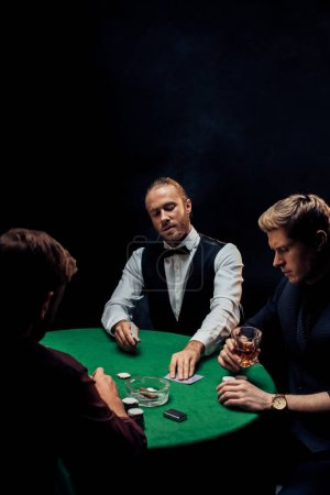 Photo pour KYIV, UKRAINE - AUGUST 20, 2019: selective focus of bearded croupier putting playing cards on poker table near men on black with smoke - image libre de droit